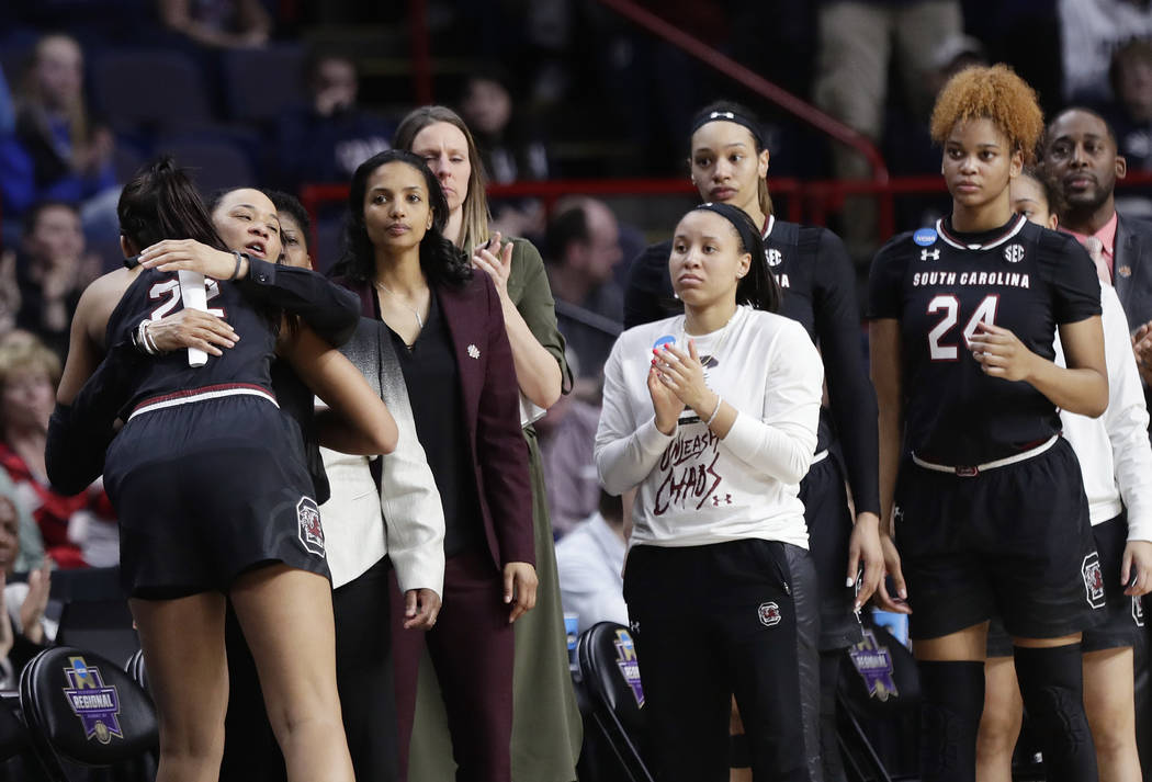 South Carolina head coach Dawn Staley hugs A'ja Wilson, left, as Wilson leaves the game during the second half of a regional final against Connecticut at the a women's NCAA college basketball tour ...