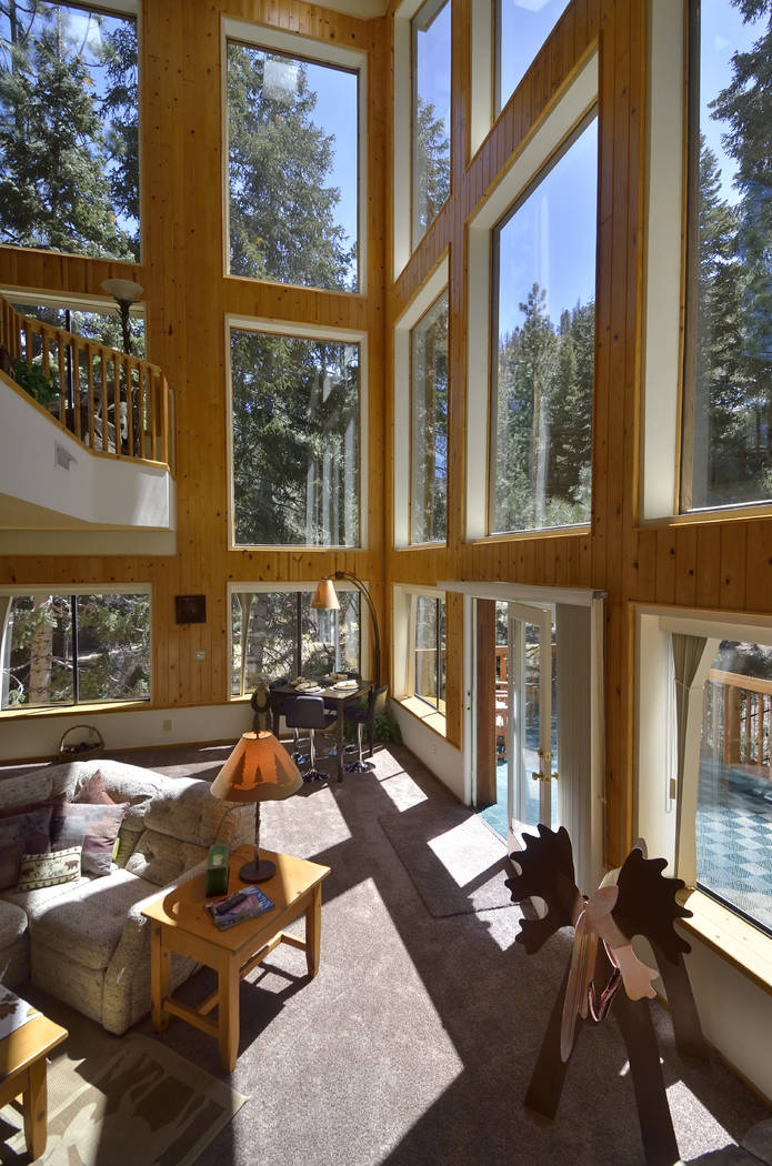 The home features a wall of windows to show off the pine forest outside. (Bill Hughes Real Estate Millions)