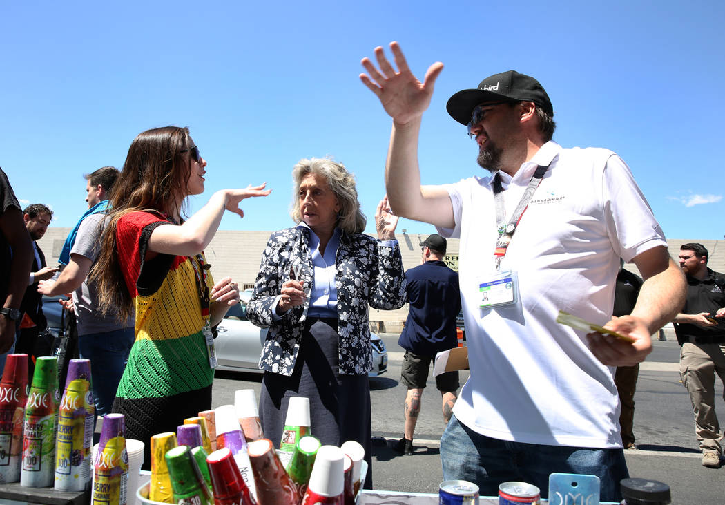 U.S. Rep. Dina Titus, D-Nev., center, talks to marijuana products vendors, Daniel Bondch, right, and Kayleigh Shea as Titus hosts a voter registration drive outside Reef Dispensaries at 3400 W. Av ...