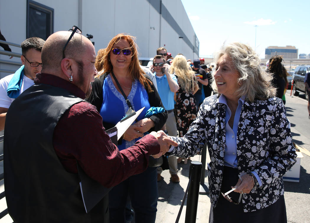 A customer, who declined to give his name, shakes hands with U.S. Rep. Dina Titus, D-Nev., right, while holding voters registration form as Titus hosts a voter registration drive outside Reef Disp ...
