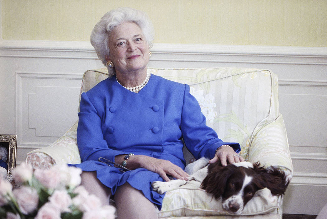 First lady Barbara Bush poses with her dog Millie in Washington in 1990. (AP Photo/Doug Mills, File)