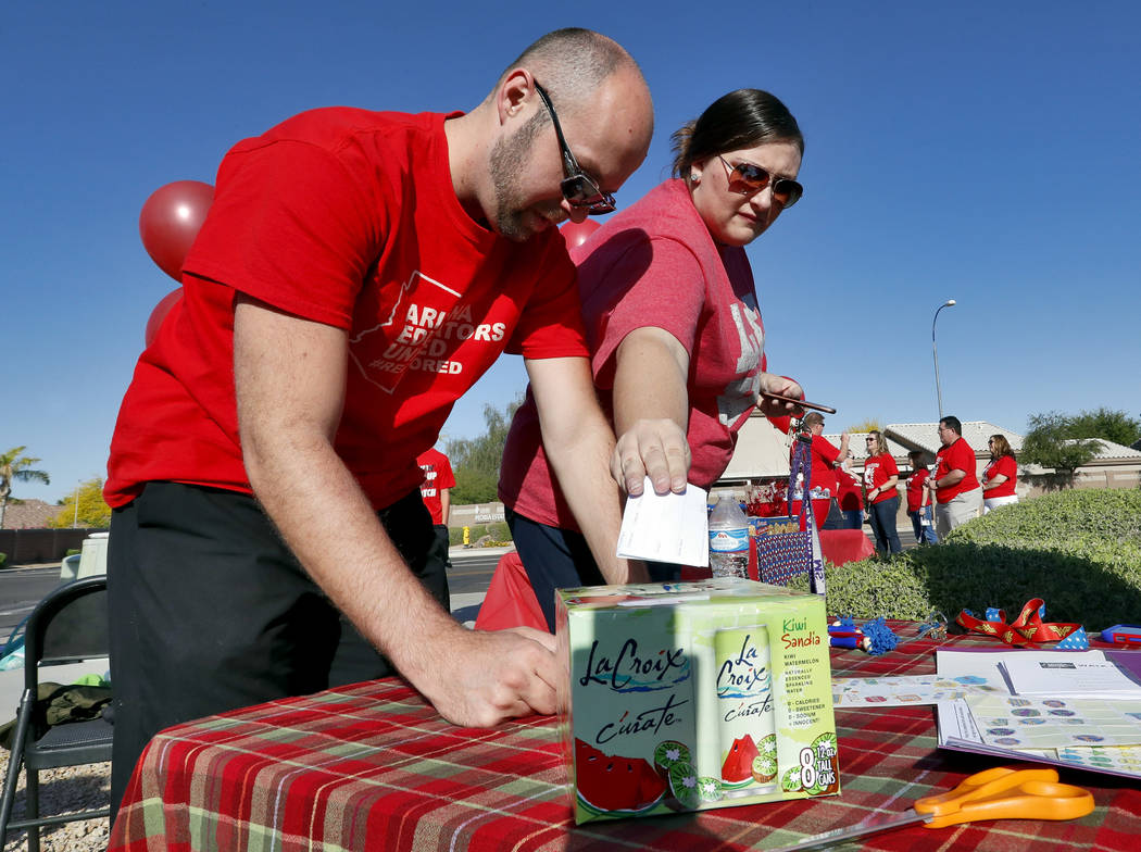 Teachers Cassi Igo and Andrew Brothers cast their ballots outside Paseo Verde Elementary Wednesday, April 18, 2018 in Peoria, Ariz. (AP Photo/Matt York)
