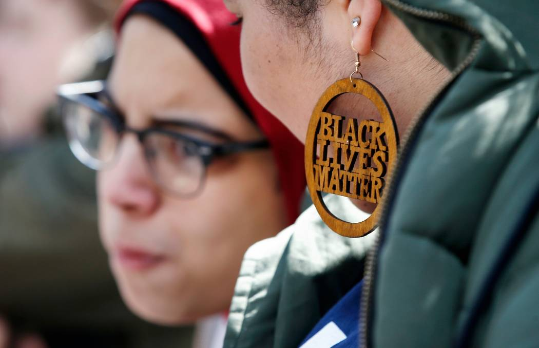 Harvard University student Cecilia Nunez wears a Black Lives Matter earring during a rally against school shootings and gun violence on the steps of Widener Library on campus in Cambridge, Mass., ...