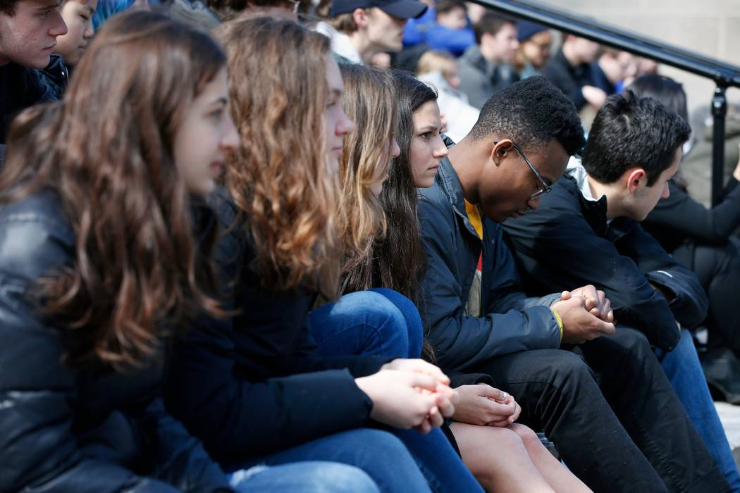 Harvard University students observe a moment of silence during a protest against school shootings and gun violence on the steps of Widener Library on campus in Cambridge, Mass., Friday, April 20, ...