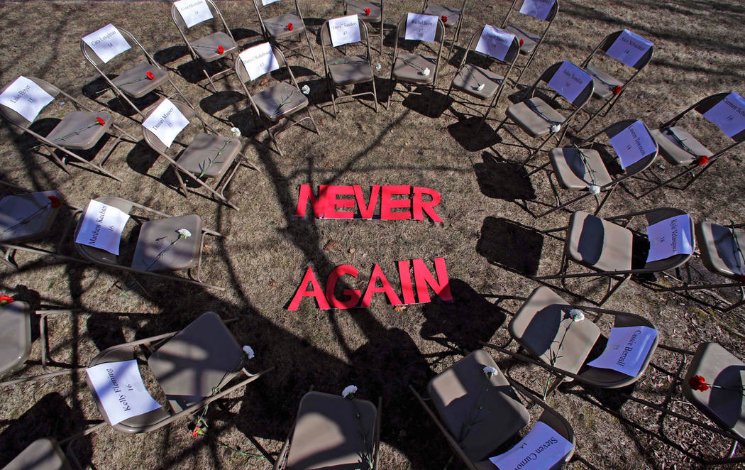 """Two rings of chairs encircle the words """"NEVER AGAIN"""" in a silent protest on the 19th anniversary of the Columbine High School shooting outside Trinity High School in Manchester, N.H., Fr ..."""