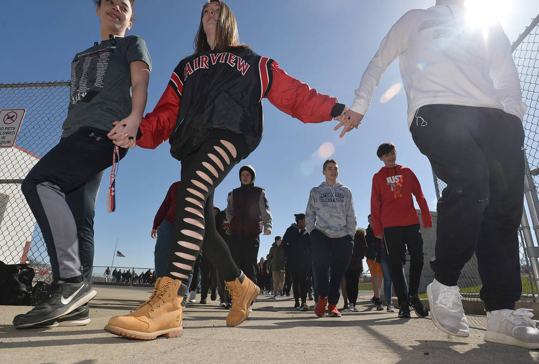 Students, from left, Nariah Marzka, 14, Morgan Orelski, 15, and Travis Burge, 15, who joined about 500 students, leave Keck Field after taking part in a national school walkout event to protest gu ...