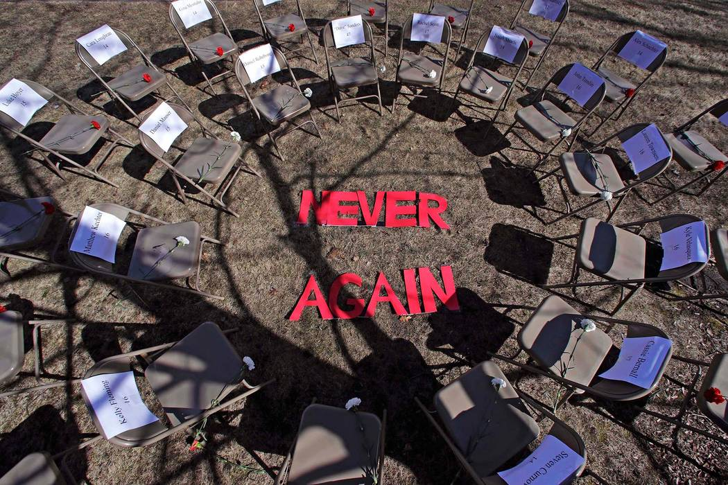 """Two rings of chairs encircle the words """"NEVER AGAIN"""" in a silent protest on the 19th anniversary of the Columbine High School shooting outside Trinity High School in Manchester, N.H., Friday, Apri ..."""