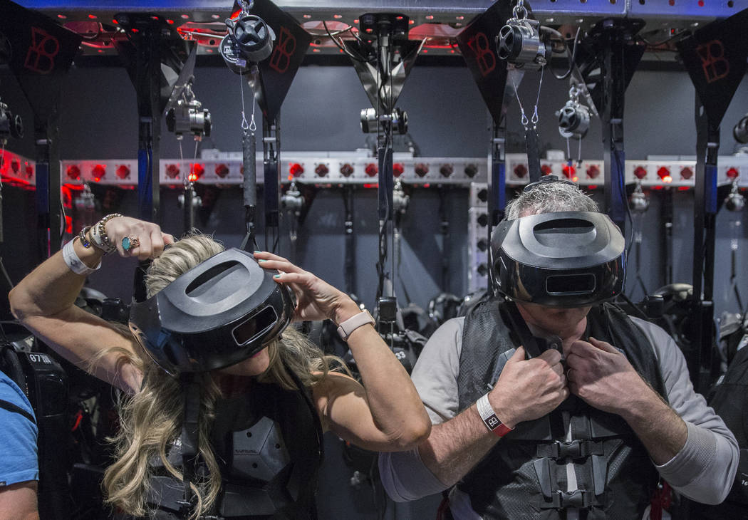 "Audra Harrison, left, and husband Buzz get their gear straightened out before the start of the new ""Star Wars: Secrets of the Empire"" VR experience at the Grand Canal Shoppes on Tuesday, ..."