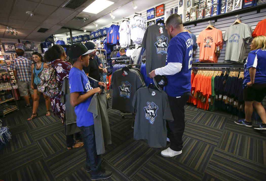 """Nine-year-old Antonio Gonzalez, left, and Jesus Gonzalez, look at shirts featuring the special Las Vegas 51s """"Reyes de Plata"""" (Silver Kings) name, part of a new Minor League Baseball in ..."""