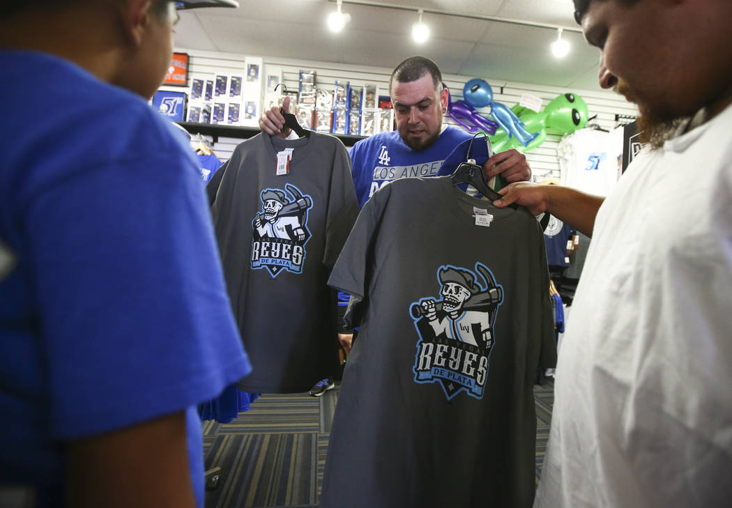 """Jesus Gonzalez, center, checks out shirts featuring the special Las Vegas 51s """"Reyes de Plata"""" (Silver Kings) name, part of a new Minor League Baseball initiative, at the team store at C ..."""