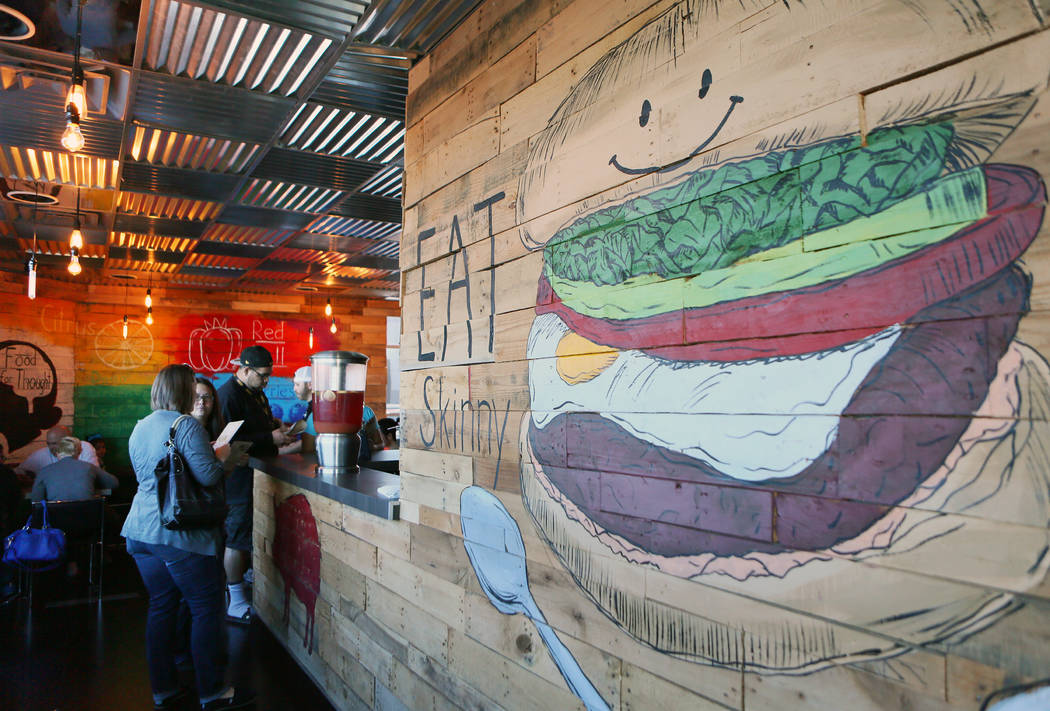 Customers wait at the counter near a mural at SkinnyFats Saturday, Dec. 6, 2014, in Las Vegas. SkinnyFats, located at 6261 Dean Martin Drive, features a split menu that has both healthful and indu ...