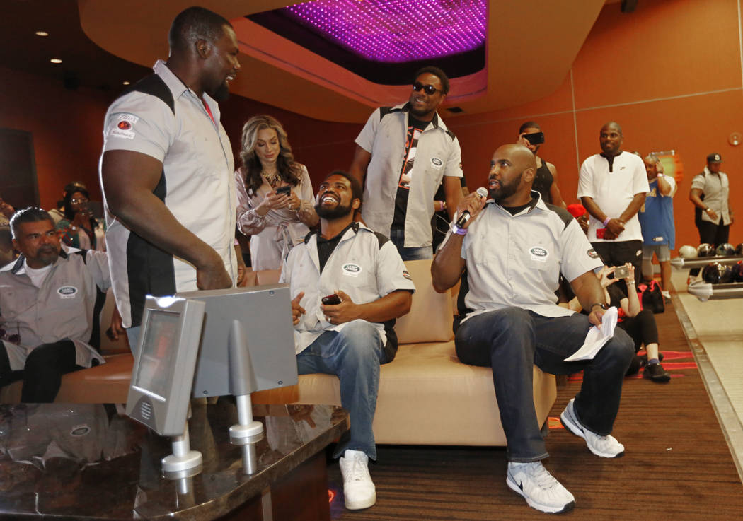 Hasim Rahman, former boxing champion, left, talks with Pro Football Hall of Fame member Jonathan Ogden, center, and Ephraim Salaam, former NFL player, right, during the Ogden Celebrity Bowl a ...