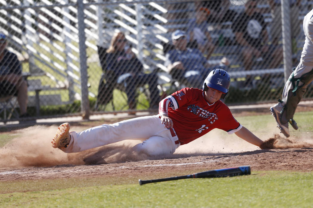Liberty's Tyler Williamson (12) slides home for a run against Green Valley during the fourth inning of the baseball game at Liberty High School in Henderson, Friday, April 20, 2018. Green Valley ...