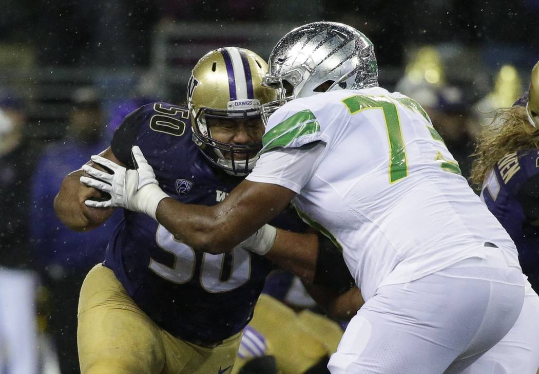 Washington defensive lineman Vita Vea, left, blocks Oregon offensive lineman Tyrell Crosby, right, in the first half of an NCAA college football game, Saturday, Nov. 4, 2017, in Seattle. (AP Photo ...