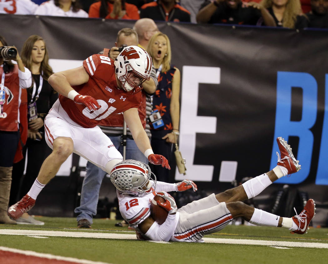 Ohio State cornerback Denzel Ward intercepts a pass intended for Wisconsin tight end Troy Fumagalli, left, during the first half of the Big Ten championship NCAA college football game, Saturday, D ...
