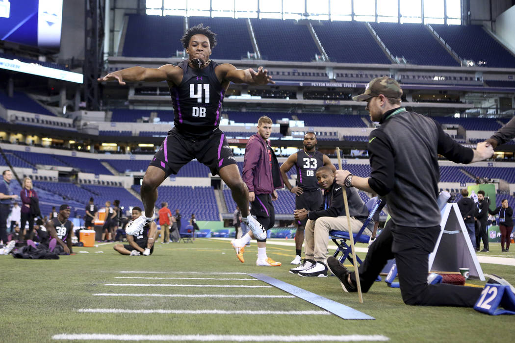 Ohio State defensive back Denzel Ward competes in the Broad Jump at the 2018 NFL Scouting Combine on Monday, March 5, 2018, in Indianapolis. (AP Photo/Gregory Payan)
