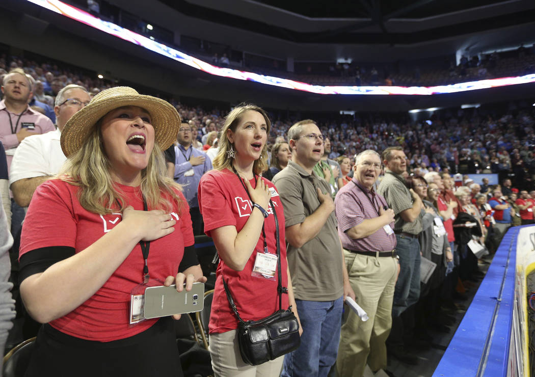 Amy Loveless, left, along with other delegates, sing the National Anthem to open the Utah Republican 2018 nominating convention Saturday, April 21, 2018, in West Valley City, Utah. (AP Photo/Georg ...