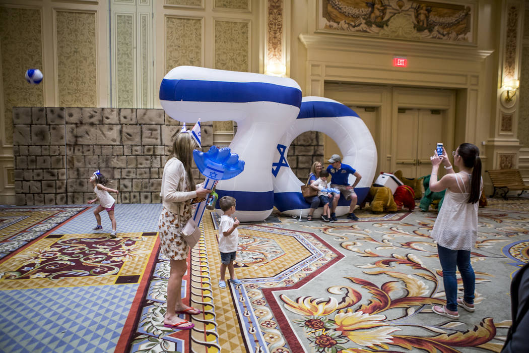 People celebrate and take photos in front of a large inflatable 70 to commemorate Israel's 70th Independence Day during the Celebrate Israel Day Festival at the Palazzo Ballroom in The Venetian on ...