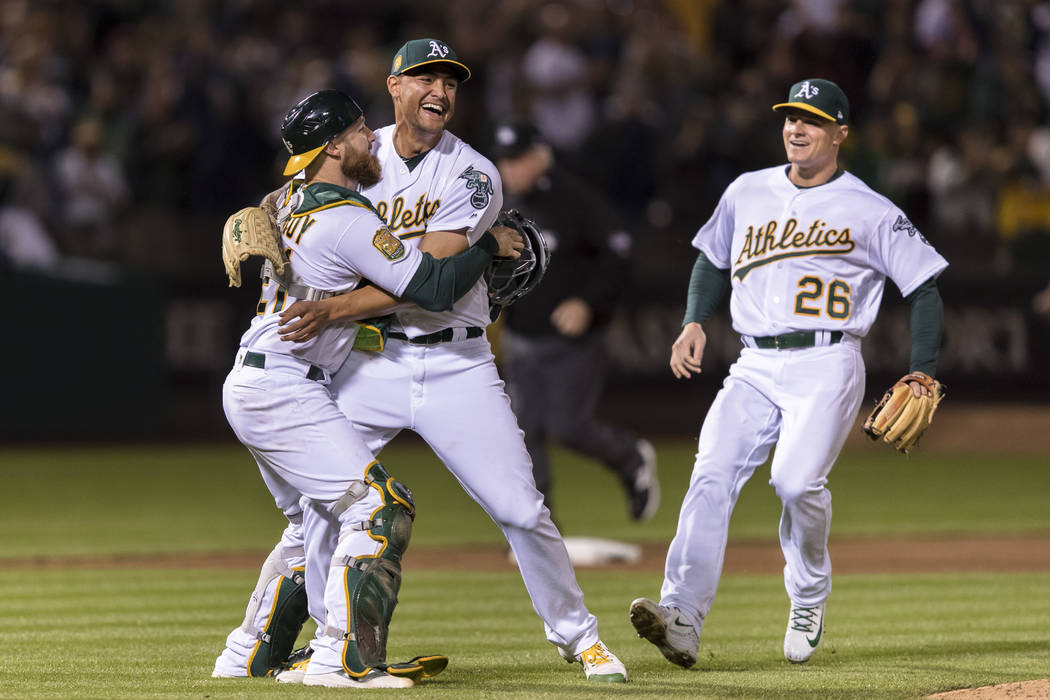 Oakland Athletics starting pitcher Sean Manaea, center, celebrates with catcher Jonathan Lucroy after pitching a no-hitter against the Boston Red Sox in a baseball game in Oakland, Calif., Saturda ...