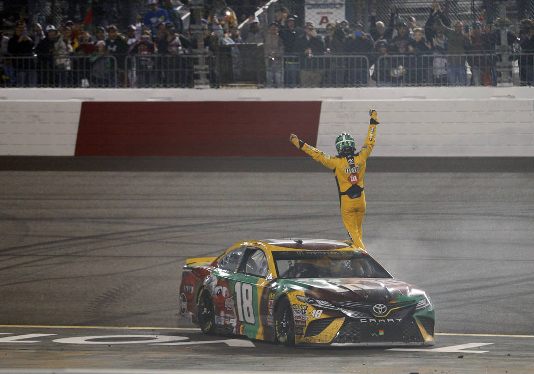 Kyle Busch waves to the fans as he celebrates winning the NASCAR Cup Series auto race at Richmond Raceway in Richmond, Va., Saturday, April 21, 2018. (AP Photo/Steve Helber)