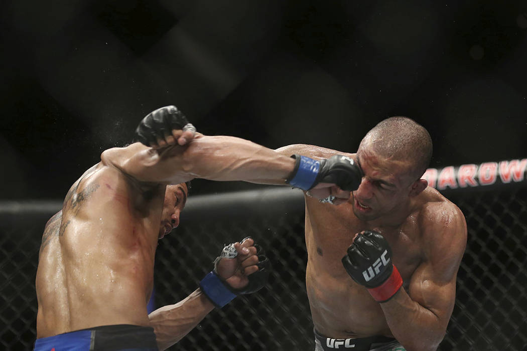 Kevin Lee, left, hits Edson Barboza during the fourth round of their mixed martial arts lightweight bout, early Sunday, April 22, 2018, in Atlantic City, N.J. Lee won the bout. (AP Photo/Mel Evans)