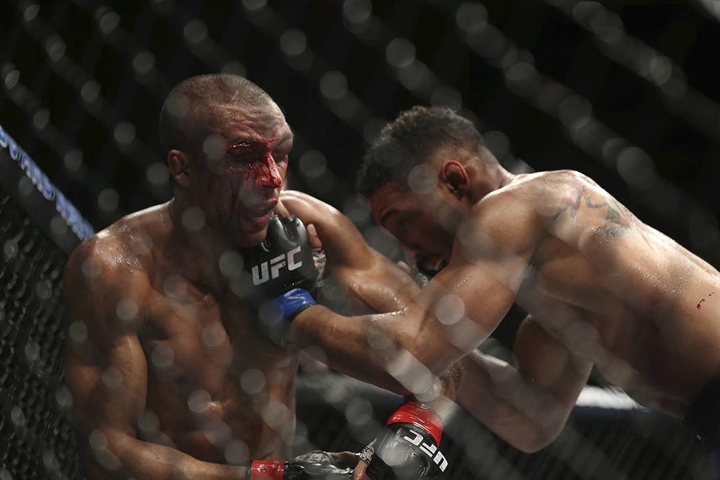 Kevin Lee, right, hits Edson Barboza during the fourth round of their mixed martial arts lightweight bout, early Sunday, April 22, 2018, in Atlantic City, N.J. Lee won the bout. (AP Photo/Mel Evans)