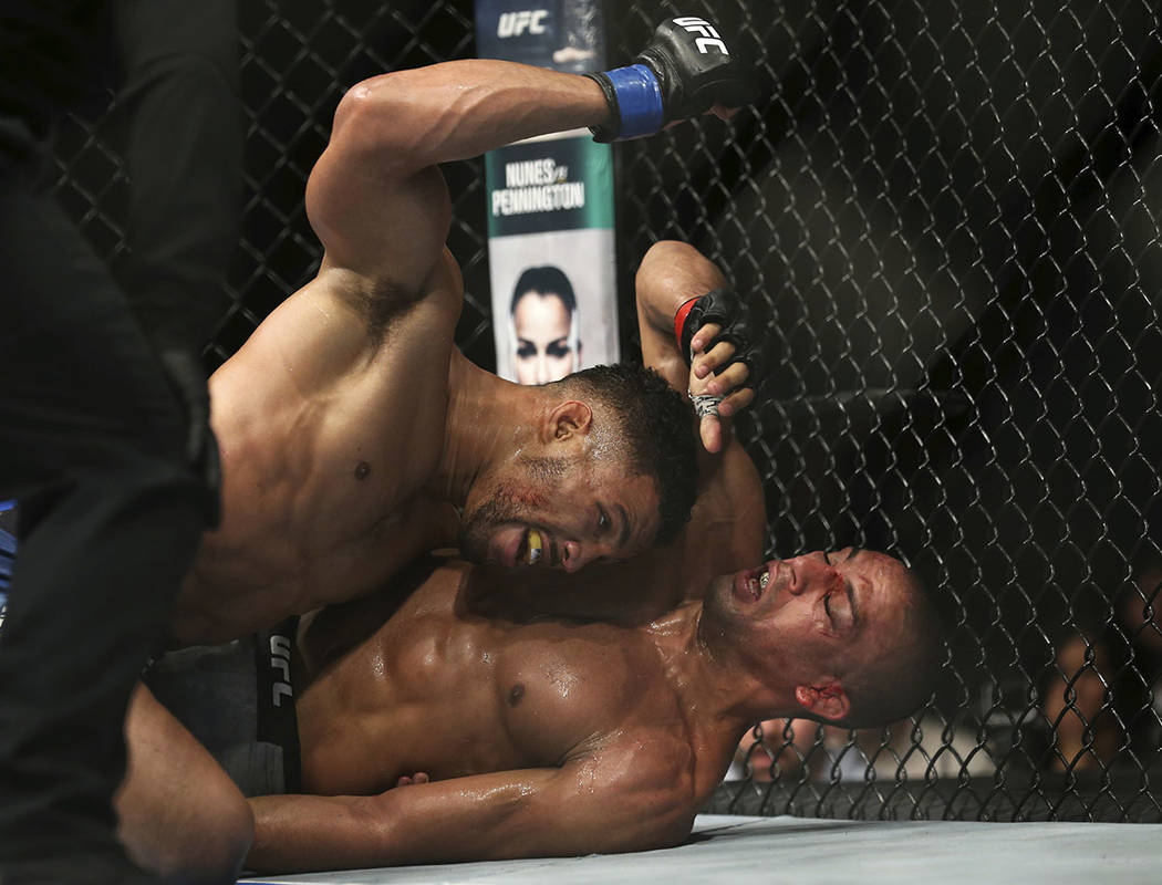 Edson Barboza, bottom, tries to protect himself as Kevin Lee hits him during the second round of their mixed martial arts lightweight bout, early Sunday, April 22, 2018, in Atlantic City, N.J. Lee ...