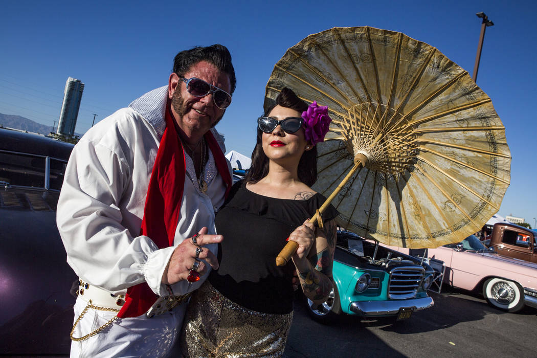 "Patrick ""P.J."" Anderson of Mesquite, dressed as Elvis, stands in front of classic cars with Yaya Ibarra of San Diego at Viva Las Vegas at The Orleans on Saturday, April 21, 2018. Patri ..."