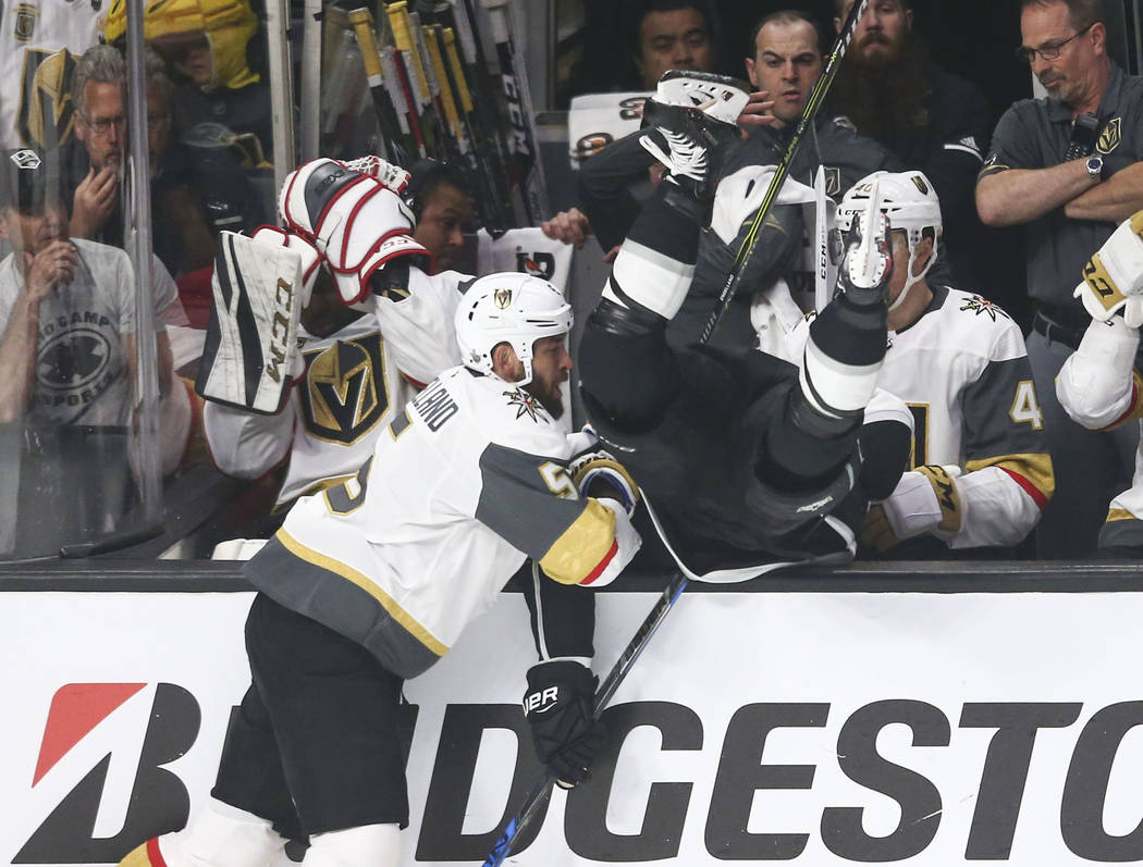Golden Knights defenseman Deryk Engelland (5) knocks Los Angeles Kings left wing Kyle Clifford (13) into the bench during the second period of Game 4 of an NHL hockey first-round playoff series at ...