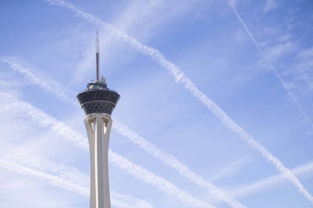 Vapor trails left behind by airplanes are seen above the Stratosphere tower in Las Vegas. (Richard Brian/Las Vegas Review-Journal) @vegasphotograph