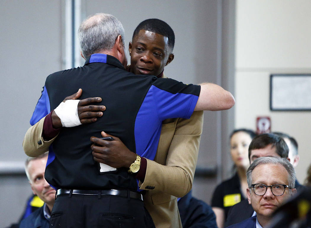 James Shaw, right, gets a hug from Waffle House CEO Walt Ehmer during a press conference on the Waffle House shooting Sunday, April 22, 2018 in Nashville, Tenn. Shaw wrestled the gun from the susp ...
