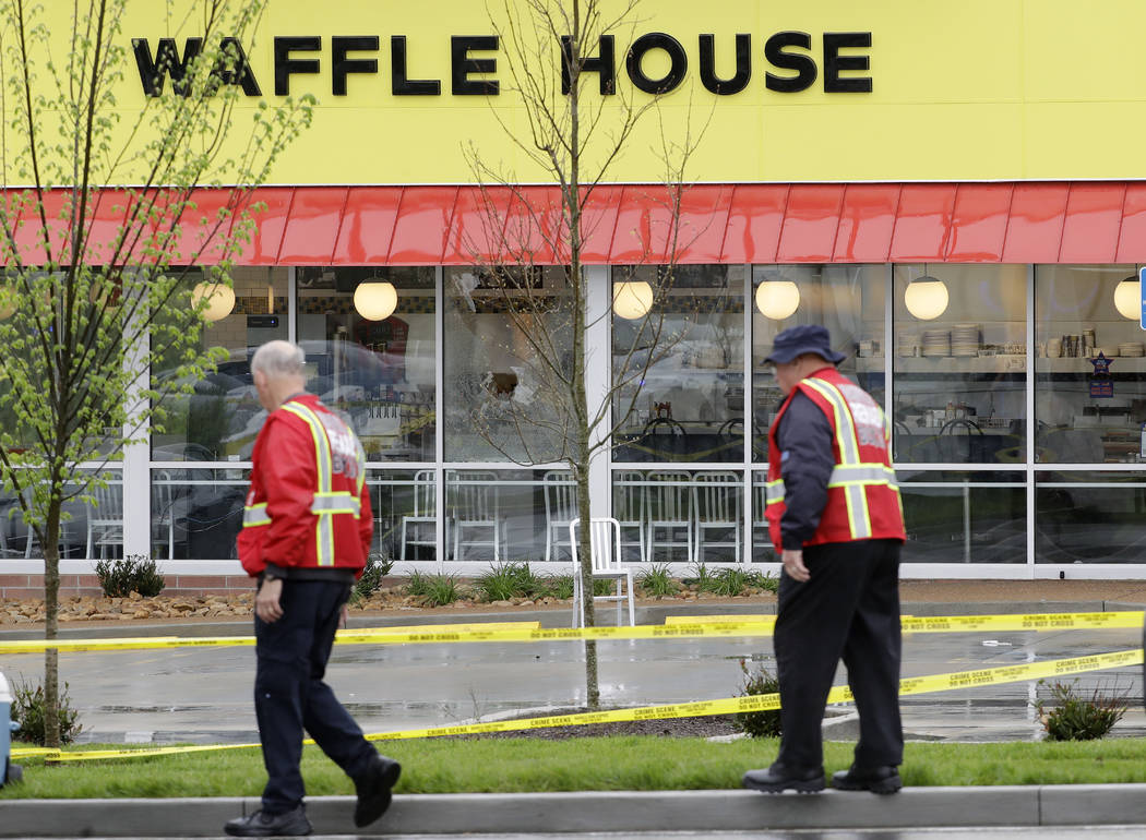 Emergency workers walk outside a Waffle House restaurant Sunday, April 22, 2018, in Nashville, Tenn. At least four people died after a gunman opened fire at the restaurant early Sunday. (Mark Hump ...