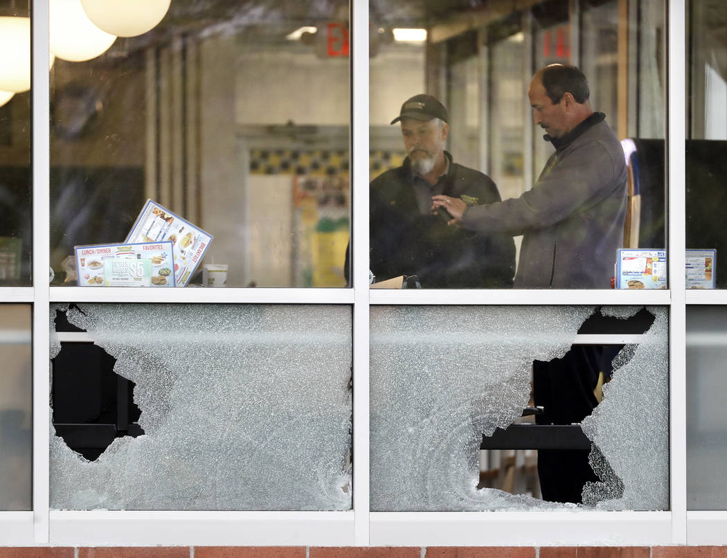 People look over an area near a window shot out at a Waffle House restaurant Sunday, April 22, 2018, in Nashville, Tenn. Several people died after a gunman opened fire at the restaurant early Sund ...