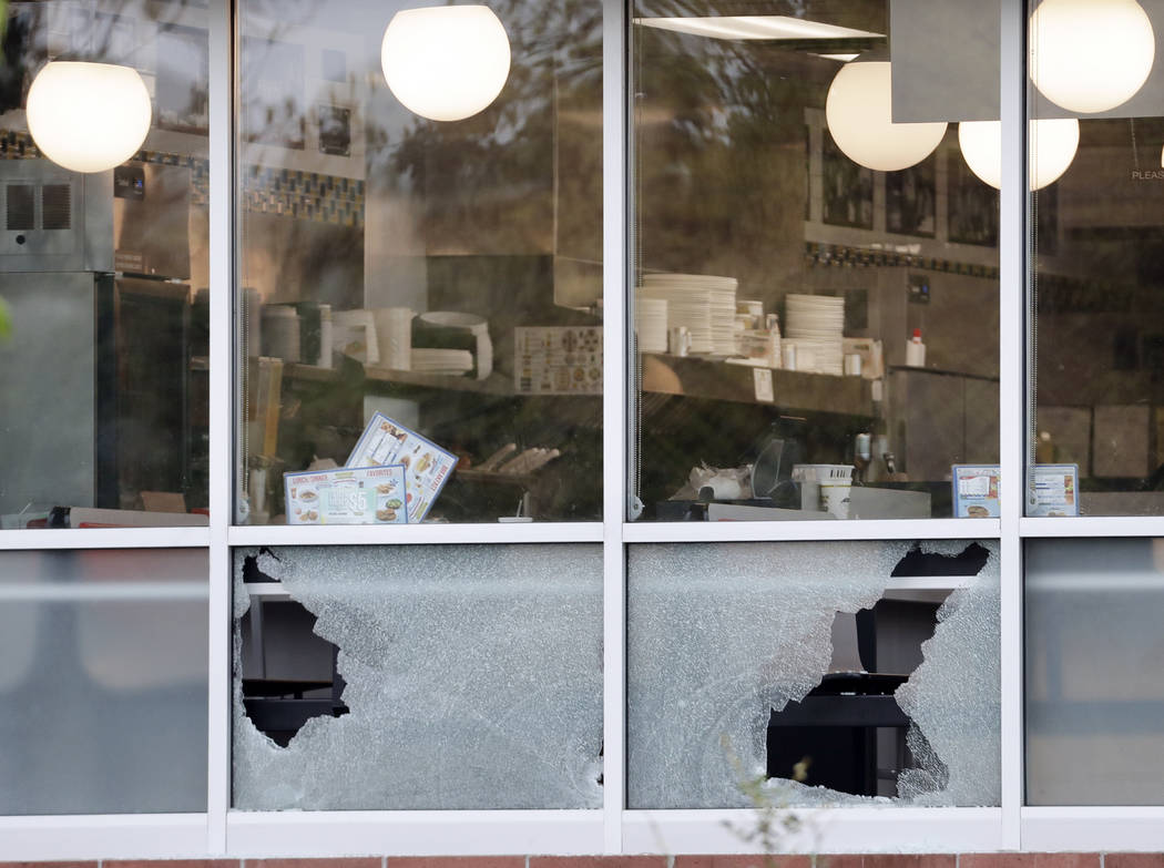 Menus sit on tables next to windows shot out at a Waffle House restaurant Sunday, April 22, 2018, in Nashville, Tenn. At least four people died after a gunman opened fire at the restaurant early S ...