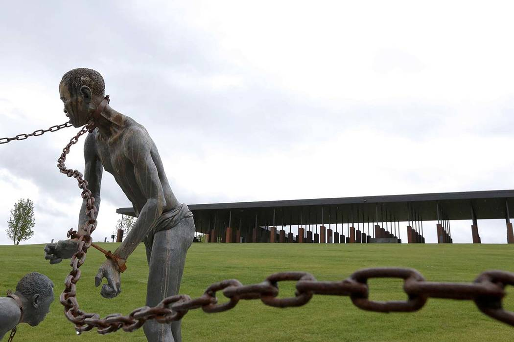 A statue of a chained man is on display at the National Memorial for Peace and Justice, a new memorial to honor thousands of people killed in racist lynchings, Sunday, April 22, 2018, in Montgomer ...