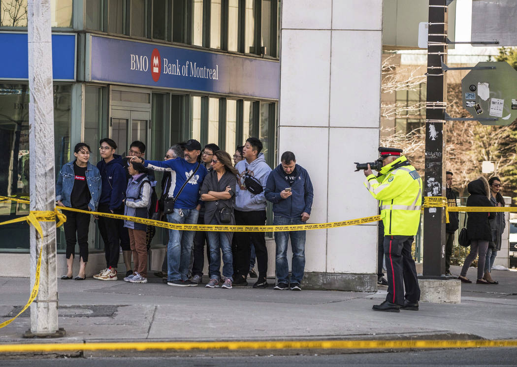 A police officer takes pictures of the scene as emergency services close Yonge Street in Toronto after a van mounted a sidewalk crashing into a crowd of pedestrians on Monday, April 23, 2018. The ...