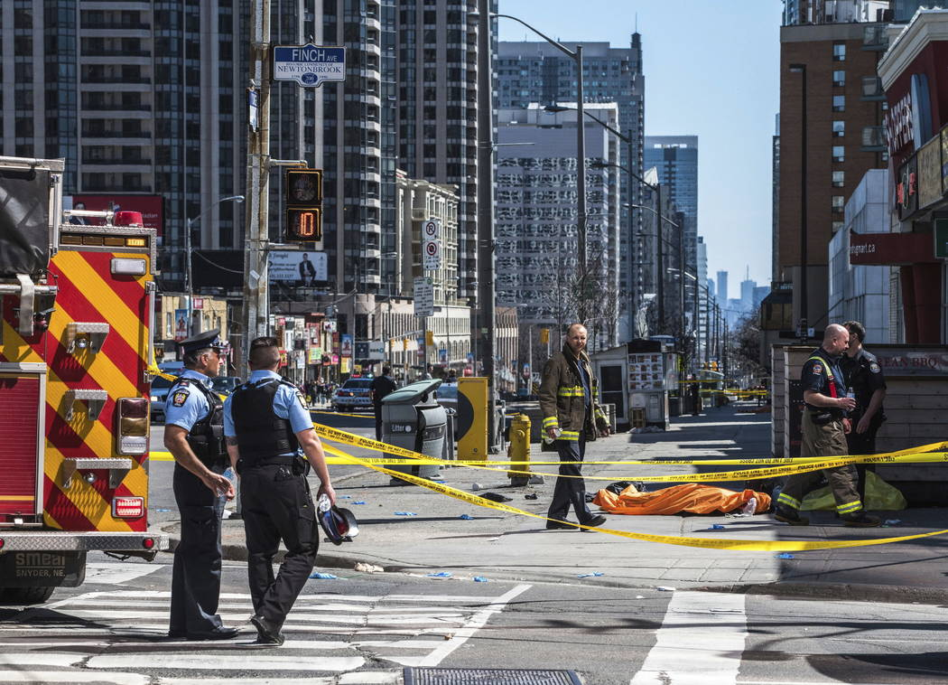 A body lies covered on the sidewalk in Toronto after a van mounted a sidewalk crashing into a number of pedestrians on Monday, April 23, 2018.A van apparently jumped a curb Monday in a busy inters ...