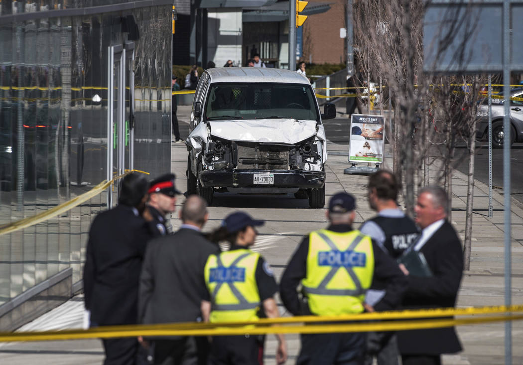 Police are seen near a damaged van after a van mounted a sidewalk crashing into pedestrians in Toronto on Monday, April 23, 2018. The van apparently jumped a curb Monday in a busy intersection in ...