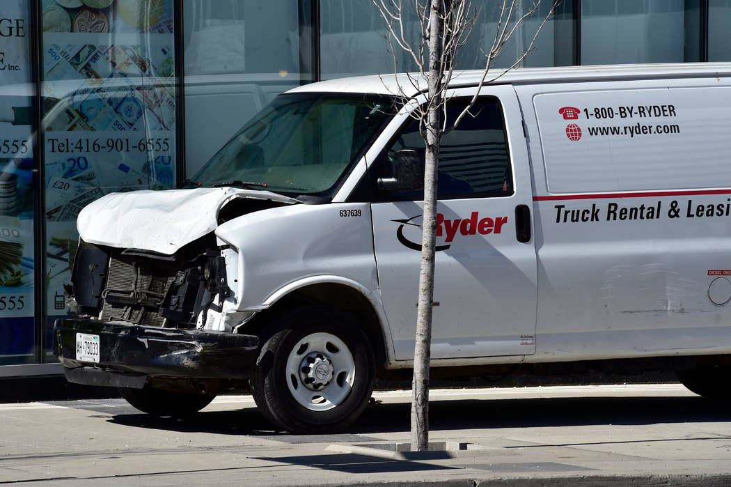 A van with a damaged front-end sits idle on a sidewalk after the driver drove down a sidewalk crashing into a number of pedestrians in Toronto, Monday, April 23, 2018. The van apparently jumped a ...