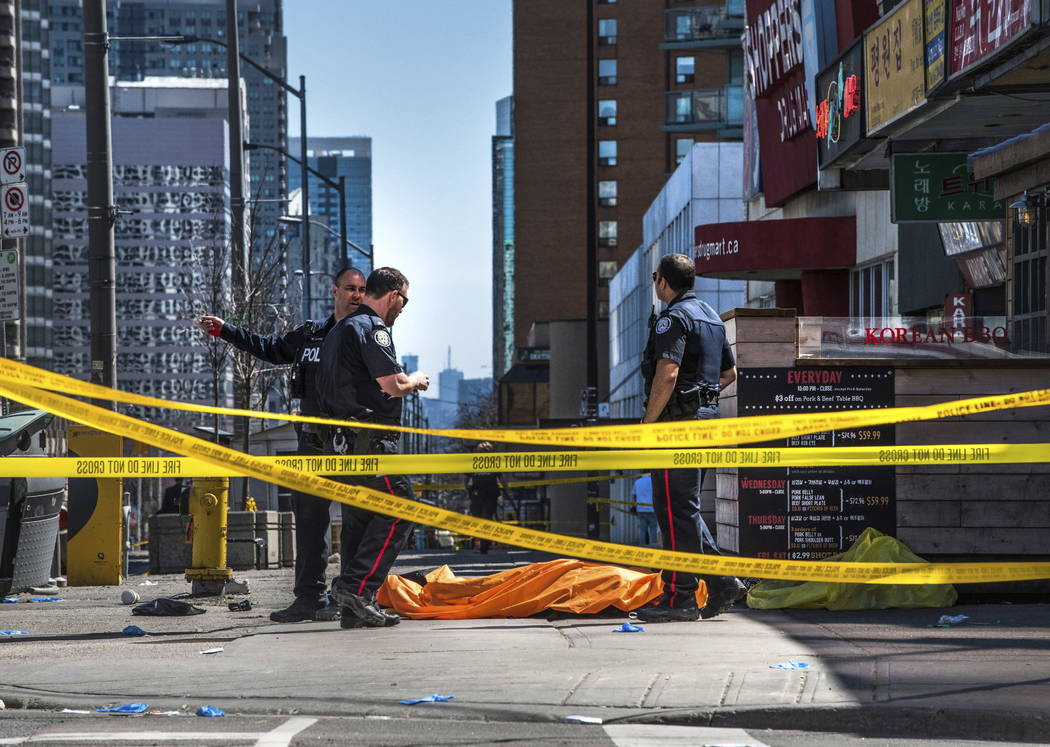 Police officers stand by a covered body in Toronto after a van mounted a sidewalk and crashed into a crowd of pedestrians on Monday, April 23, 2018. The van apparently jumped a curb Monday in a bu ...