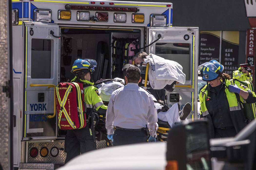 A van jumped a curb in a Toronto intersection and struck at least eight pedestrians on Monday, April 23, 2018. (Aaron Vincent Elkaim/The Canadian Press via AP)