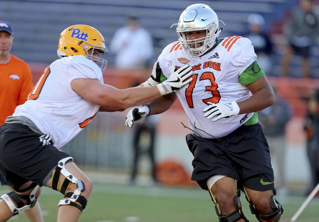 North Squad offensive tackles Tyrell Crosby of Oregon (73) and Brian O'Neill of Pittsburgh (70) run drills during the North team's practice for Saturday's Senior Bowl college football game in Mobi ...