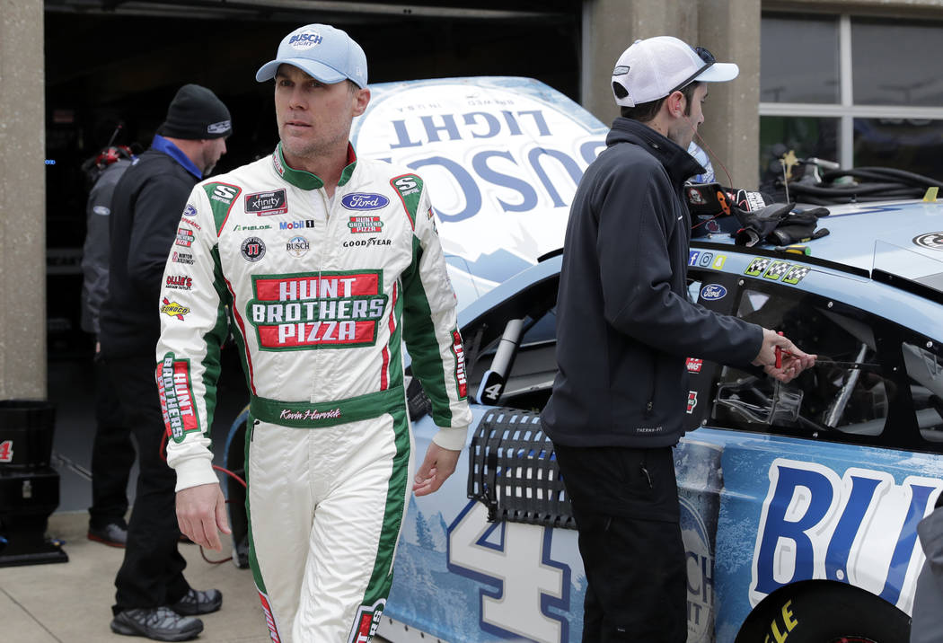 Kevin Harvick walks through the garage area as members of his team make adjustments to his car after a practice session for a NASCAR Cup series auto race in Fort Worth, Texas, Saturday, April 6, 2 ...