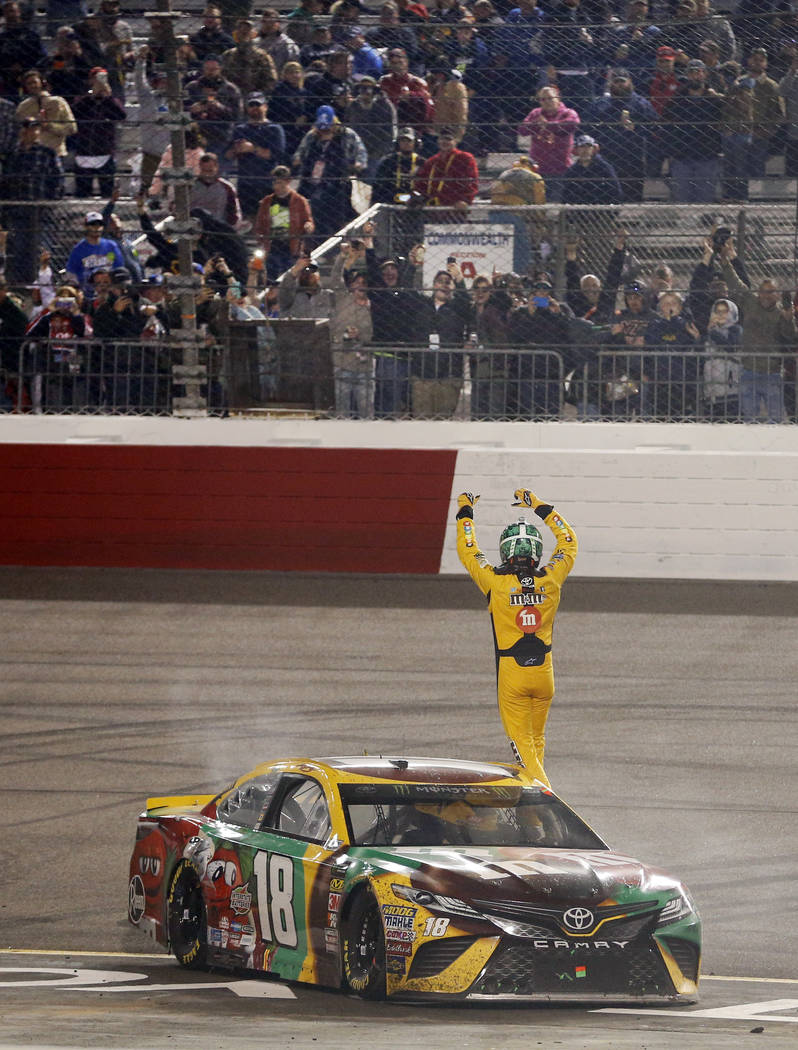 Kyle Busch waves to the fans as he celebrates after winning the NASCAR Cup Series auto race at Richmond Raceway in Richmond, Va., Saturday, April 21, 2018. (AP Photo/Steve Helber)