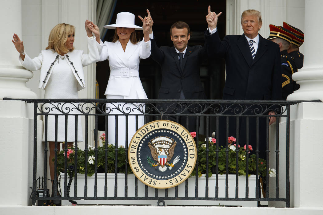 Brigitte Macron, first lady Melania Trump, French President Emmanuel Macron, and President Donald Trump join hands during a State Arrival Ceremony on the South Lawn of the White House, Tuesday, Ap ...