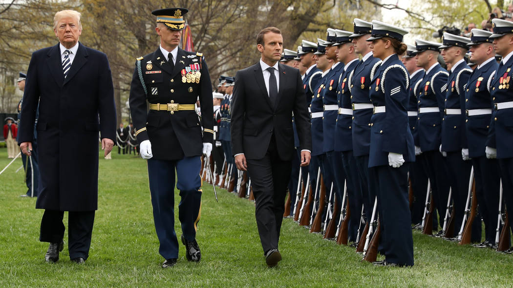 President Donald Trump and French President Emmanuel Macron review the troops during a State Arrival Ceremony on the South Lawn of the White House in Washington, Tuesday, April 24, 2018. (AP Photo ...