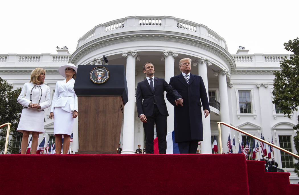 President Donald Trump and French President Emmanuel Macron, right, with first lady Melania Trump and Brigitte Macron, left, hold hands on stage during a State Arrival Ceremony on the South Lawn o ...