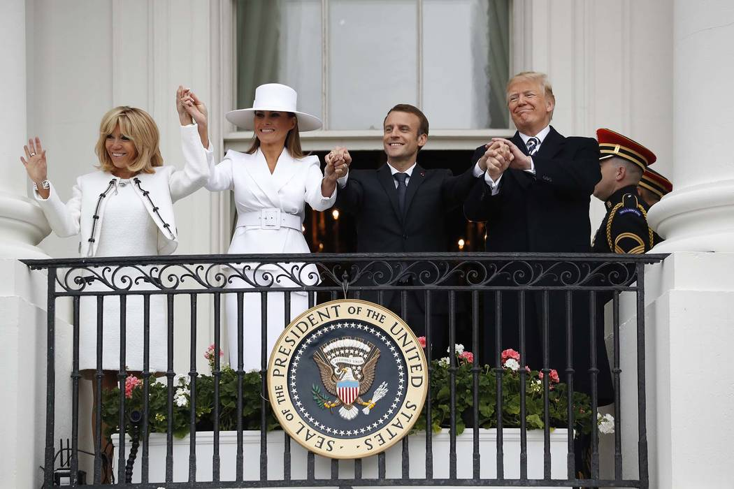 President Donald Trump, French President Emmanuel Macron, first lady Melania Trump and Brigitte Macron hold hands on the White House balcony during a State Arrival Ceremony at the White House in W ...