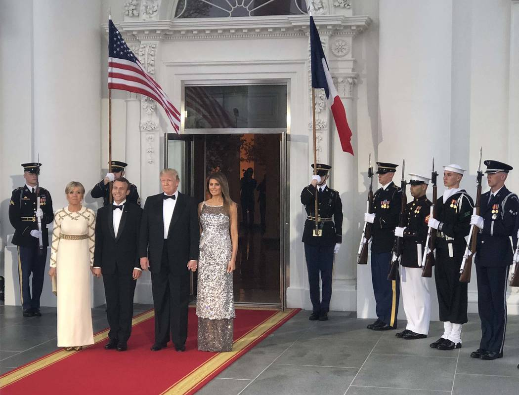 President Donald Trump and first lady Melania Trump stand with French President Emmanuel Macron and his wife, Brigitte, at the North Portico of the White House before a state dinner, Tuesday, Apri ...
