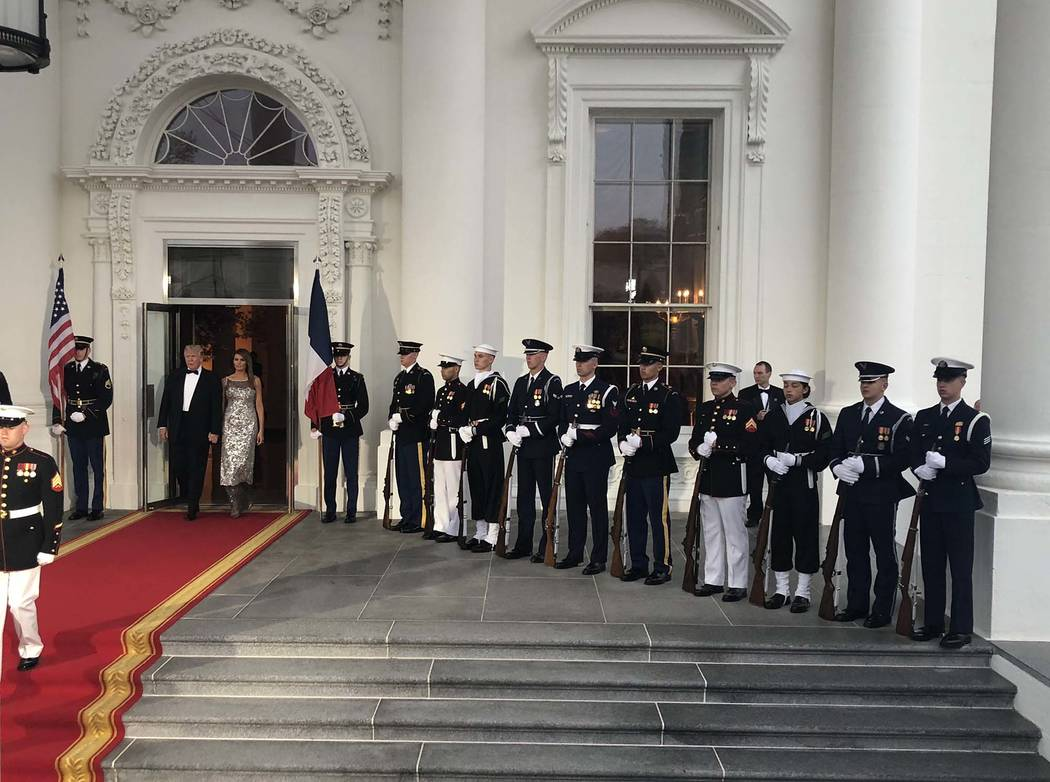 President Donald Trump and first lady Melania Trump walk out to the North Portico of the White House to greet the French president, Emmanuel Macron, and his wife before a state dinner, Tuesday, Ap ...